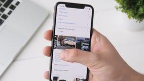 Yekaterinburg Ryssland - Oktober 3, 2018: Man som använder det Google sökandet app på smartphonen för iPhone som X bläddrar till  lager videofilmer