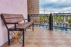 Yekaterinburg, Sverdlovsk Russia - 09 28 2018: A beautiful wooden painted brown color bench with black wrought-iron legs with gold stock images