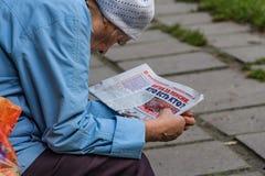 Yekaterinburg Sverdlovskaya/Ryssland - 08 28 2018: En äldre kvinna i ett blått omslag och en vit hatt läser a royaltyfria foton