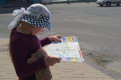 YELETS/LIPETSK OBLAST, RÚSSIA - 8 DE MAIO DE 2017: a menina de oito anos considera o guia da cidade Foto de Stock Royalty Free