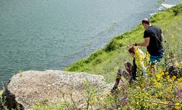 Yelets, Russia, July 2017: A man helps a girl to descend from a slope, look at the river. A man helps a girl to descend from a slope, look at the river Royalty Free Stock Images