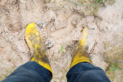 Yelkow Muddy rubber boots on wet silt Stock Photos