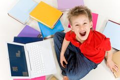 Yelling. Above view of screaming kid sitting among textbooks with laptop near by Royalty Free Stock Images