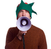 Yelling Elf. An adult Christmas elf is using a megaphone to yell at the viewer and is isolated against a white background Stock Images