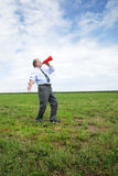 Yelling in a megaphone. Senior business man shooting a message through a red megaphone in  a meadow Royalty Free Stock Photos