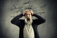 Yelling senior man with closed eyes holding his head by hands Royalty Free Stock Photos