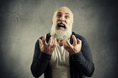 Yelling senior man over grey background Royalty Free Stock Images