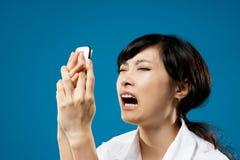 Yelling woman. Yelling, closeup portrait of Asian business woman on studio blue background Stock Image