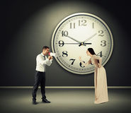 Yelling woman and screaming man. Angry yelling women and screaming men with megaphone in dark room with big clock on the wall Stock Photography