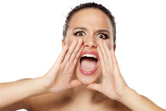 Yelling woman. Young woman shouting at you with hands next to her mouth Royalty Free Stock Image
