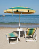 Yelllow and Green Beach Umbrella. A green and yellow striped  beach umbrella and deckchairs on a beach on a sunny summers day Stock Image