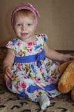 使用和摆在与玩具熊的愉快的一岁的女孩 图库摄影