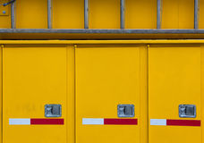 Yellow Abstract – side of emergency vehicle. Close-up side of a yellow emergency vehicle with 3 doors and red and white stripes stock photo