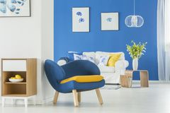 Yellow accents in blue room. Yellow accents in blue and white living room interior with wooden cupboard, blue armchair and white sofa Stock Photo
