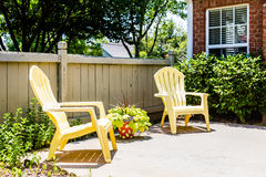 Yellow Adirondack Chairs on Patio Stock Photography