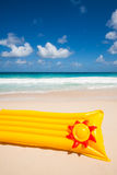 Yellow air mattress and frisbee Stock Images