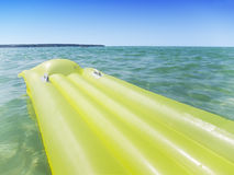 Yellow airbed in the sea. Empty yellow airbed floating in the sea Stock Photo