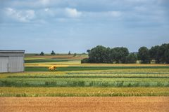 Multicolored agricultural fields and an airplane royalty free stock image