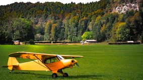 Yellow airplain on the green grass. On the mountain Royalty Free Stock Photography