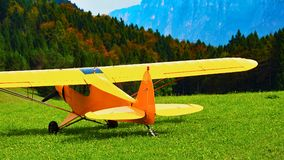 Yellow airplain on the green grass mountain in a sunny day. Yellow airplain on the green grass mountain Stock Image