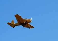 Yellow airplane. Flying airplane on the blue sky royalty free stock photography