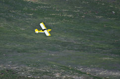 Yellow Airplane Flying Through the Canyon Stock Photography