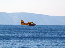 Yellow airplane flying near sea Royalty Free Stock Photo