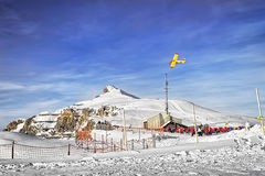 Yellow airplane flying over alpine resort in swiss alps in winte Royalty Free Stock Photo