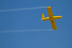 Yellow airplane speeds by with blue sky. One person jet airplane flys in blue sky. Smoke on wingtips gives accents Stock Image