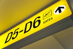Yellow airport direction departure sign. Detailed  view of yellow airport departure sign showing direction to gates Stock Photo