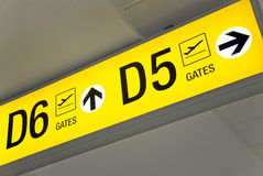 Yellow airport direction departure sign. Detailed  view of yellow airport departure sign showing direction to gates Stock Photography