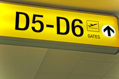 Yellow airport direction departure sign. Detailed  view of yellow airport departure sign showing direction to gates Royalty Free Stock Photo