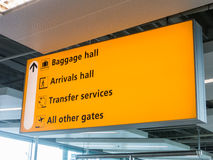 Yellow airport sign. Airport sign directing passengers to baggage/arrivals hall, transfer services and other gates royalty free stock photography