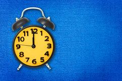 yellow alarm clock on blue carpet stock image