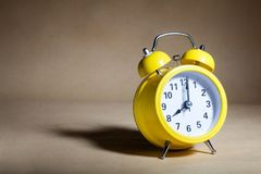 Yellow alarm clock. On brown background stock image