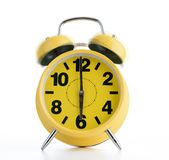Yellow alarm clock rings in the morning on white background. Time to wake up Stock Image