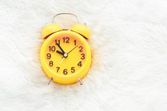 Yellow alarm clock on white wool. Late and Lazy time concept. Morning in holiday theme. Around 10 O Clock. Furniture, isolated, face, plastic, fuel, bed, wake stock photography