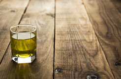 Yellow alcohol shot drink. On wooden background Royalty Free Stock Images