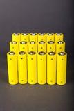 Yellow alkaline batteries. An array of yellow alkaline batterieson grey background Stock Photos