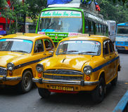 Yellow Ambassador taxi cars go on the street in Kolkata Stock Photos