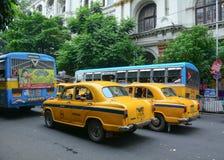 Yellow Ambassador taxi cars go on the street in Kolkata Royalty Free Stock Photo