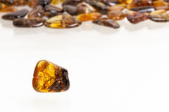 Yellow amber stone. Yellow amber stone close up on a background of other stones Stock Photography
