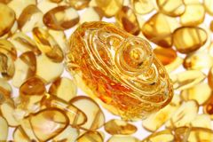 Yellow amber stones. An antique bottle close-up against a background of yellow amber stones Stock Photos