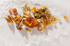 Yellow amber stones. On a white lace cloth Royalty Free Stock Image