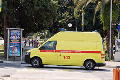 Yellow ambulance van is at the intersection of streets of the re Stock Photo