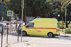 Yellow ambulance van is at the intersection of streets of the re Stock Image