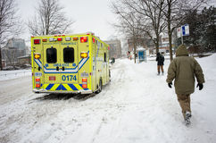 Yellow ambulance waiting on the Ontario street in Montreal. Montreal, Canada - February 16, 2016: On a freezing snowy day with rain yellow ambulance waiting on Royalty Free Stock Image