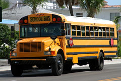 Yellow american school bus. Driving along the street stock photography
