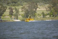 Yellow amphibious seaplane taking off from Lake Casitas, Ojai, California Royalty Free Stock Image