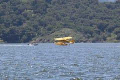 Yellow amphibious seaplane taking off from Lake Casitas, Ojai, California Royalty Free Stock Images